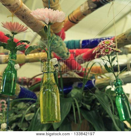 Chrysanthemum flower in diy hanging glass bottles for vase, selective focus. Square image, vintage toned effect