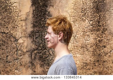 Portrait Of 16 Years Old Boy With Red Hair With Grunge Background