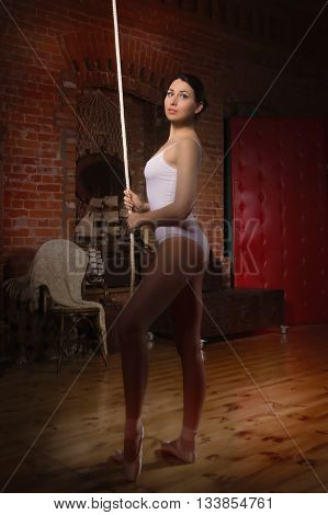 Young ballerina standing on poite in a dark room