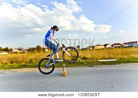 Young Boy Jumping With His Dirk Bike Over A Barrier At The Street