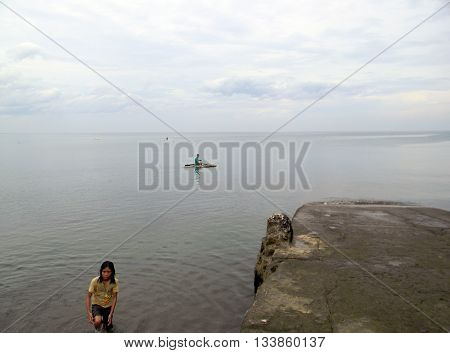 CEBU CITY, CEBU / PHILIPPINES - JULY 30, 2011: Fishermen in small outrigger canoes go fishing near a public beach in Cebu.