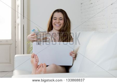young woman playing with little toy replica of shopping trolley running it on laptop computer smiling happy on sofa couch in e-commerce and internet business concept