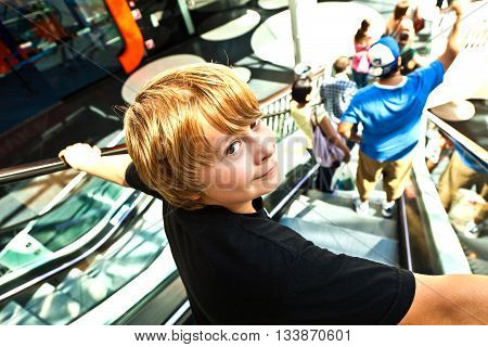 Boy On A Moving Staircase In The Shopping Center