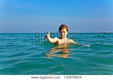 Boy With Red Hair Is Enjoying The Clear Warm Water At The Beautiful Beach