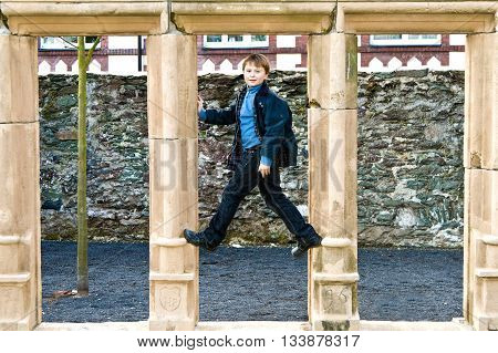 Young Boy Climbs In An Old Historic Sandstone Window