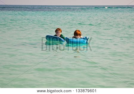Children  Swim  And Use An Air-matress For Relaxing At The Clear Sea
