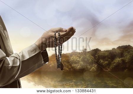 Hand of muslim people praying with lake landscape background
