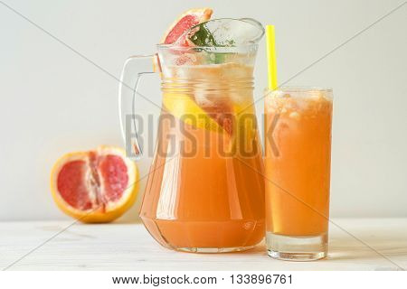 Grapefruit lemonade in jag with ice on the table