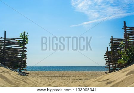 entrance to the beach over sand dunes made by woven wood branches