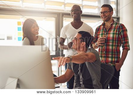 Man Showing Something On Computer To Happy Friends