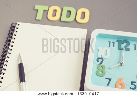 Selective focus on modern aqua blue square clock at 8 o'clock with todo wording and notebook / notepad and pen - eight o'clock on gray background - concept of time to work