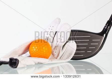 Golf driver and white glove on a glass desk