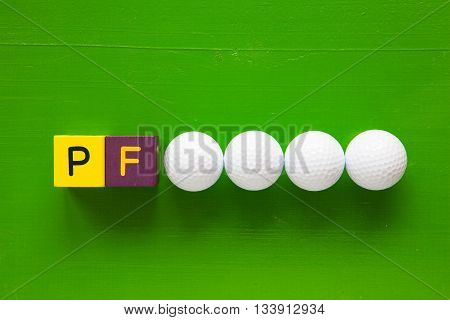 P.F. - an inscription from children's wooden blocks and golf ball - Flat Lay Photography