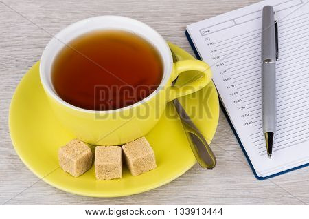 Tea In Cup, Lumpy Sugar, Notepad And Pen On Table