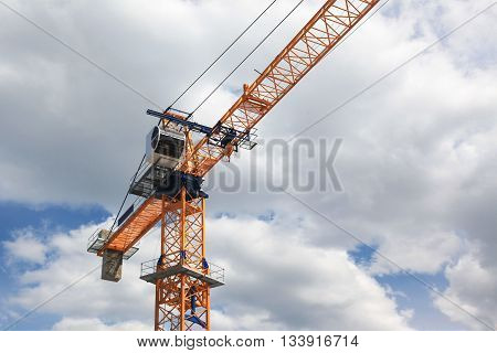 large construction crane against a blue sky with clouds