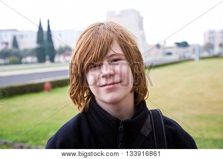 Young Boy With Red Hair Is Smiling And Looking Happy
