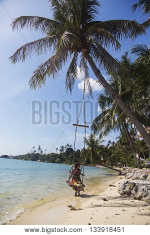 Woman on the swing at the beach in Thailand