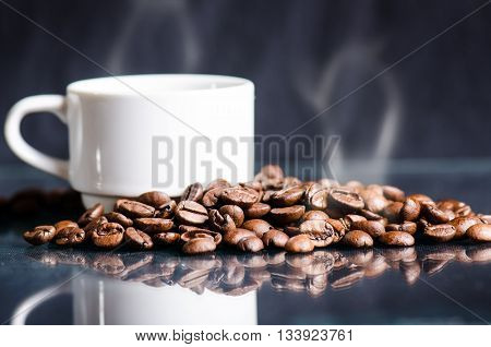 Coffee beans on a black background. Raw coffee beans. Grained product. Hot drink. Close up. Harvesting. Natural background. Energy. Reflection in a glass and coffee foam like a heart