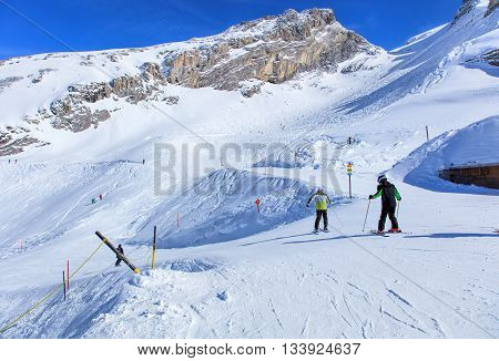 Mt. Titlis, Switzerland - 9 March, 2016: view with people skiing. Titlis is a mountain of the Uri Alps located on the border between the Swiss cantons of Obwalden and Bern mainly accessed from the town of Engelberg on the north side.