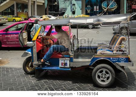 BANGKOK THAILAND - May 2016. Traditional street taxi (tuk-tuk)  in front of a common pink taxi on a busy shopping street in the center of Bangkok, Thailand. In Bangkok there are more than 100000 (tuk-tuk).