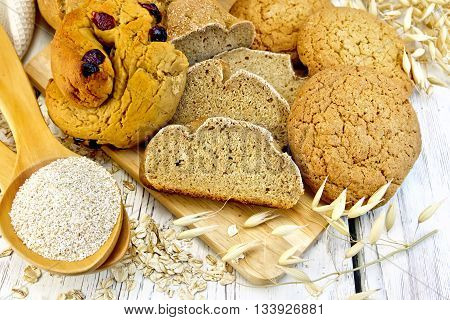 Bread, rolls and biscuits oat, bran in a spoonful, oat stalks on a background of wooden boards