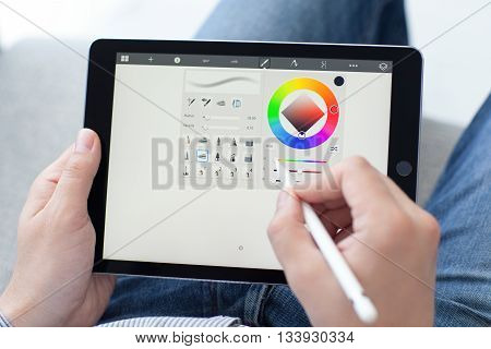 Alushta Russia - May 14 2016: Man with Apple Pencil holding in the hand iPad Pro. iPad Pro was created and developed by the Apple inc.