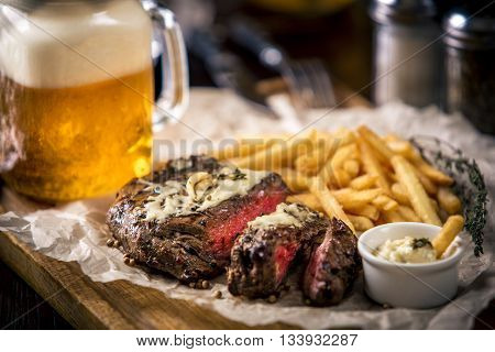 Healthy lean grilled medium-rare steak with french fries, and beer, and a spice in a rustic pub or tavern. Food-styling
