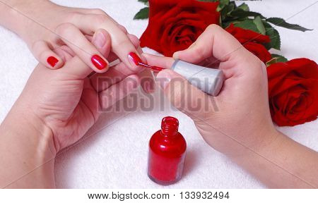 aplication of red polish with roses on background closeup