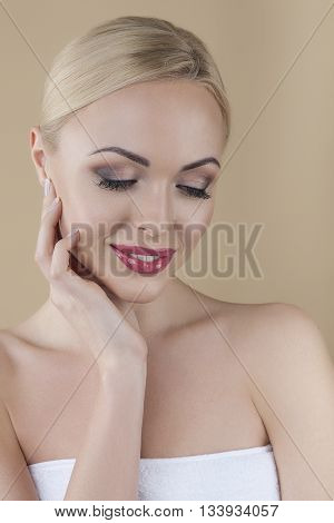 Beautiful young woman touching her cheek, posing in studio isolated on brown background