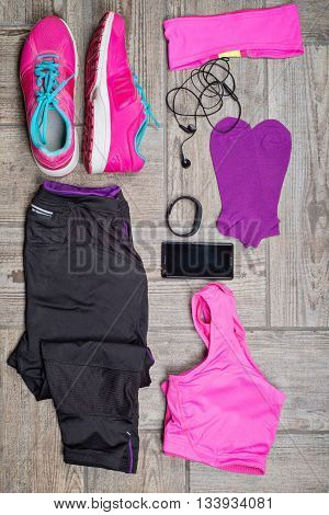Flat lay shot of woman's sport accessories. Leggins, sneakers, earphones, phone and top. Ready to do some workout.