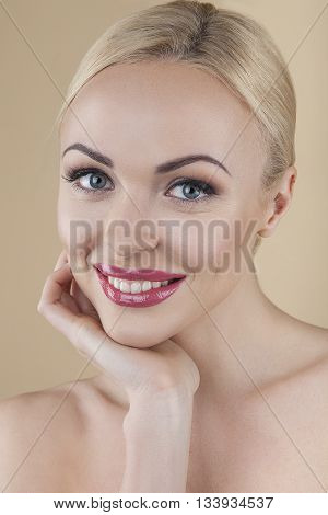 Close up of beautiful young woman with perfect skin isolated on brown background in studio