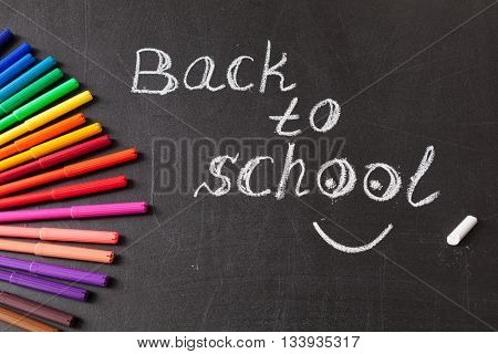 "Back to school background with colorful felt tip pens and title ""Back to school"" written by white chalk on the chalkboard poster"