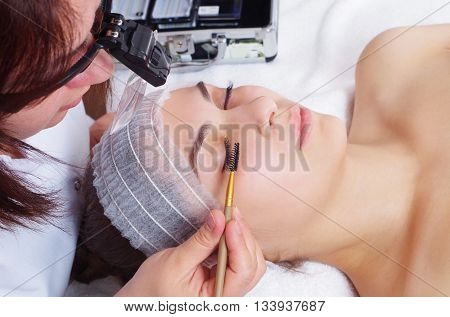 young beautiful girl is getting eyelash extentions closeup