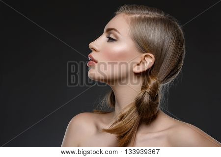Profile of beautiful young woman with blue makeup and hair nods. Beauty shot. Over dark grey background. Close-up.