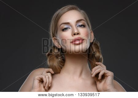 Beautiful young woman with blue makeup and hair nods. Beauty shot. Over dark grey background. Close-up.