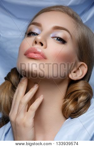 Beautiful young woman with blue makeup and hair nods. Beauty shot. Over blue textile background. Close-up.