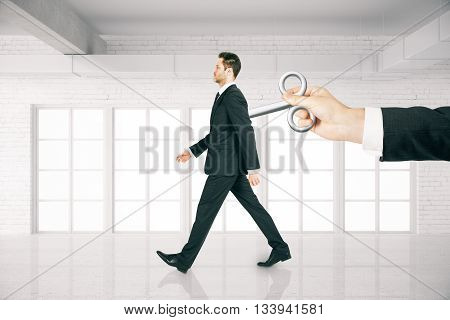 Hand activating walking businessman with a wind-up key on his back in white brick room. Concept of control