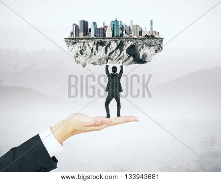 Businessman miniature standing on hand and upholding abstract city on misty background