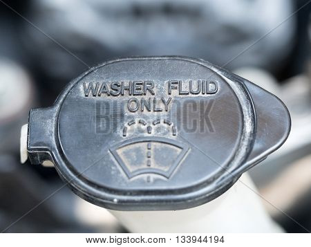 Washer fluid. Symbol of washer fluid. Close up of black washer fluid inside car engine.