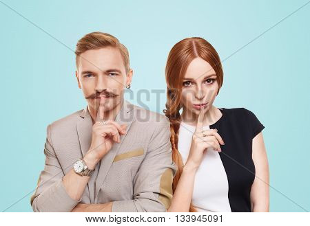 Woman and man keep secret. Couple shows hush sign, adultery, relationship issue, marriage cheating concept. Secret love, jealousy. Mystery, privacy, intimacy. Young beautiful couple isolated at blue.