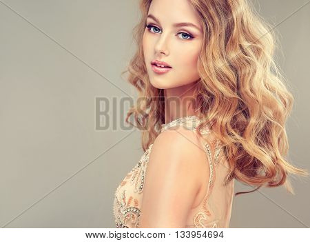 Beautiful girl light brown hair with an elegant hairstyle , hair wave ,curly hairstyle . Delicate wedding dress in cream color