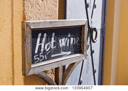 Blackboard sign with chalk letters and arrow showing direction to the hot wine selling place.