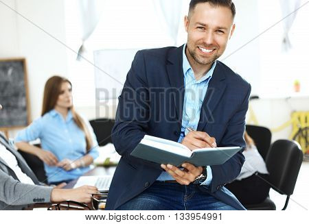 Close-up portrait of handsome confident businessman sitting at the table in office interior and attentively writing some notes in red notebook and looking at the camera with happy smile.