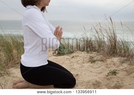 Young Woman Relaxing On The Beach With A Yoga Pose
