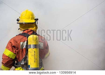 single fireman is working and surround with smoke