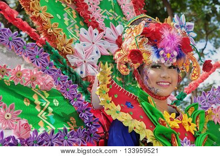 DENPASAR BALI ISLAND INDONESIA - JUNE 11 2016: Face portrait of beautiful young Balinese woman in ethnic dancer costume dancing traditional temple dance at Bali Art and Culture Festival parade.
