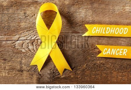 Yellow ribbon and text Childhood Cancer on wooden background