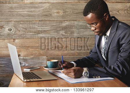 Wealthy And Serious Dark-skinned Businessman With Laptop Checking Report In Cafe With A Cup Of Coffe