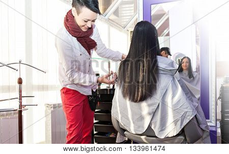 mage hair stylist hairdresser cutting woman's hair in salon with scissors and comb, a rear view of the rear side