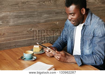 African Man Holding Digital Tablet With Both Hands, Looking With Complete Disbelief, With Mouth Open